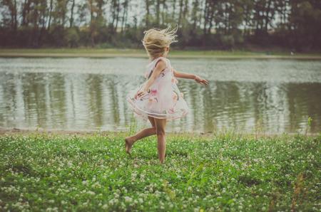 Kleines Mädchen mit dem langen blonden Haar im rosa Kleid , das zu Hause im grünen Gras durch den Fluss tanzt