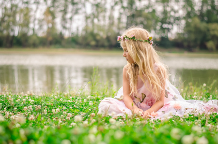 sad lonely girl with long blond hair in pink dress sitting alone as the fairy in the green grass by the river