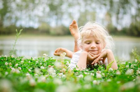 little lovely girl lying on the grass and enjoying life Stok Fotoğraf