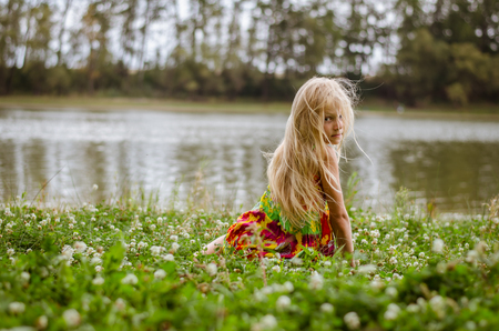 adorable caucasian girl with sad expression and long blond hair in colorful dress sitting as the fairy in the green grass by the river Stock Photo