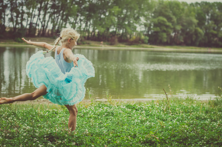 little child in blue dress dancing free in the green nature in the meadow next to the river