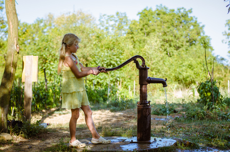 little lovely girl pumping water well to water growing vegetables in the countryside Stock Photo