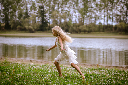 little girl with long blond hair in white dress running by the river