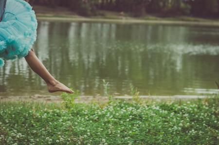 klein kind voet springen in de lucht in de groene natuur in de weide naast de rivier