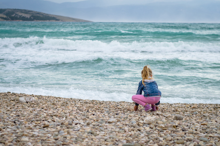little lovely blond girl on the rocky beach and wild sea