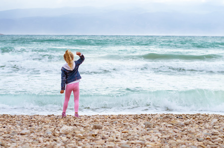 cute little blond girl with long hair throwing stones into the heavy sea Фото со стока