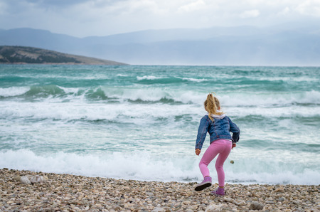 girl from back view throwing stones into heavy sea Фото со стока