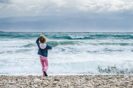 little lovely blond girl throwing stones into the heavy sea