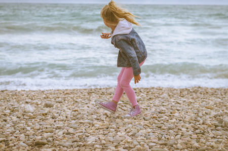 little lovely blond girl throwing stones into the sea