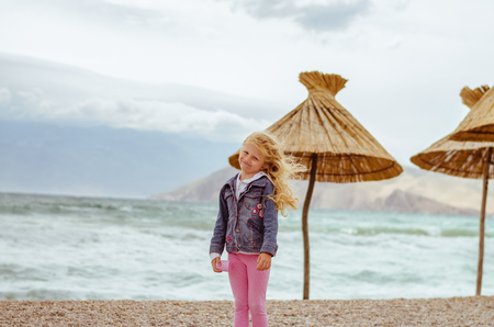 little blond girl with long hair  in the beach Фото со стока