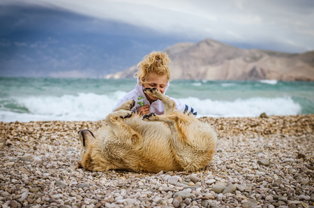 little blond girl playing with dog in bad weather in rocky beach on the Croatian coast