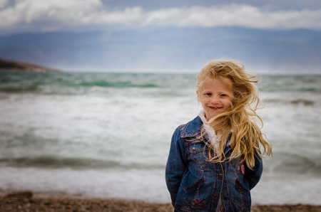 little blond girl with long hair portrait in windy weather at the sea