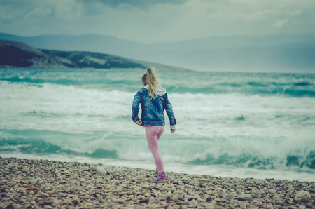 little girl running on the rocky beach with heavy sea with big waves in bad weather