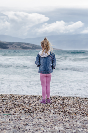 little girl back view on the rocky beach looking to the sea horizon Фото со стока