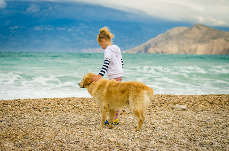 little blond girl with dog standing in rocky beach on the Croatian sea