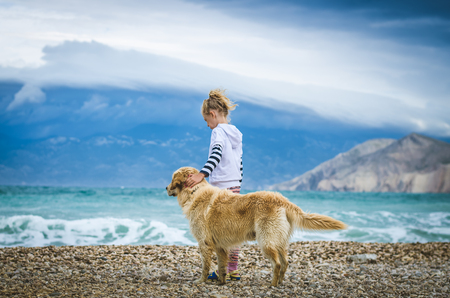 little blond girl with dog standing in rocky beach in the Croatian coast