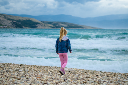 little girl back view on the rocky beach with heavy sea with big waves in bad weather