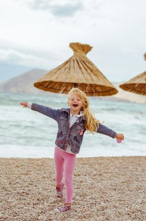 little blond girl with long hair having fun in the beach