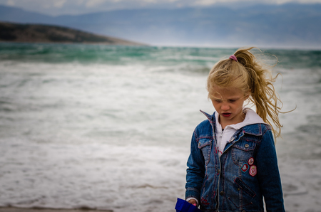 little girl portrait in windy weather at the sea