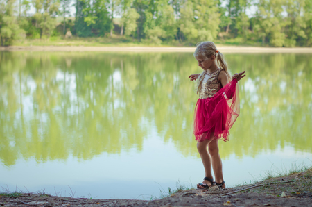 adorable blond girl dancing in the strand of the lake