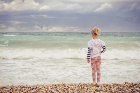 little lovely blond girl looking to the sea horizon