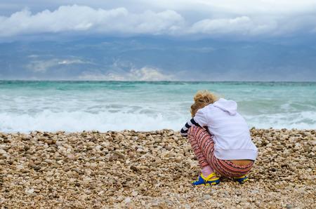 Little girl alone in rocky beach