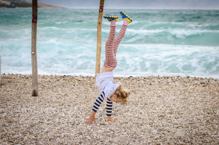 little blond girl doing gymnastics in the rocky beach by the sea