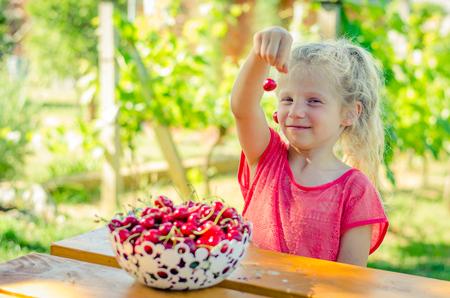 lovely blond girl eating cherry outdoors in the garden