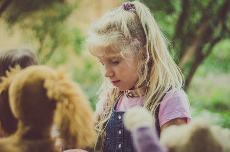 adorable blond girl with long hair playing with fluffy toys