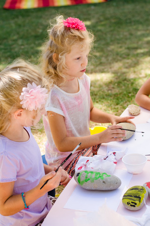 cute little blond girls having fun with painting stones