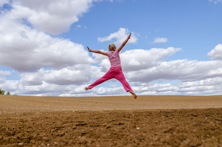 little child jumping alone in country in scenic countryside with beautiful clouds and blue sky