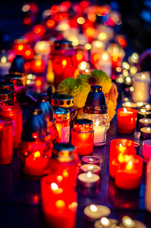 Colorful burning candles during All Saints Day at the cemetery Stock Photo