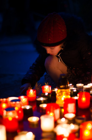 child burning candle during  All Saints Day at the cemetery at dark night Imagens