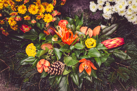 Decoration from dry colorful flowers in the cemetery at All Saints Day in autumn time