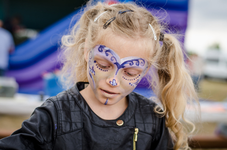 adorable blond girl with face painting portrait