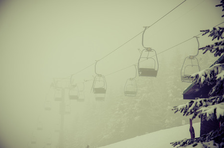 chairlift in winter resort in foggy winter Stock Photo