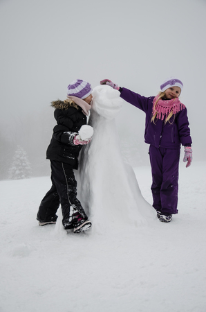 little girls in winter time building a figure of dog from snow Foto de archivo
