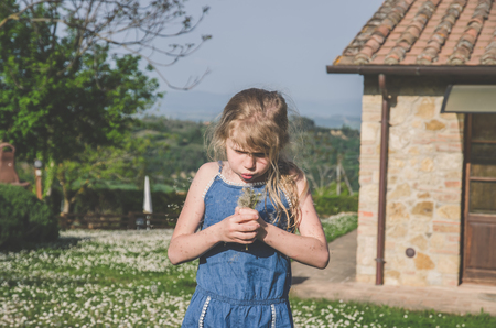 adorable little girl outdoors in meadow full of daisies and dandelions Imagens