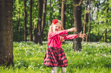 little child playing with soap bubbles outdoor in the green spring forest Reklamní fotografie