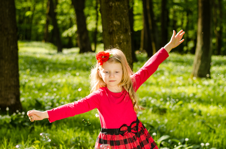 beautiful little blond girl in the green spring forest