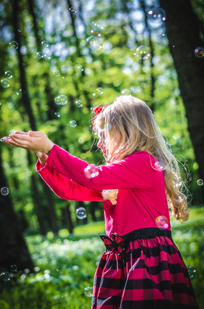 beautiful little blond girl playing with soap bubbles outdoor in the green spring forest