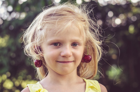 adorable blond girl with red ripe cherry fruits in ears Stock Photo