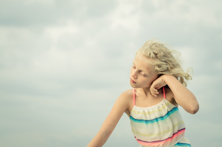 adorable little girl with blond hair portrait and blue sky