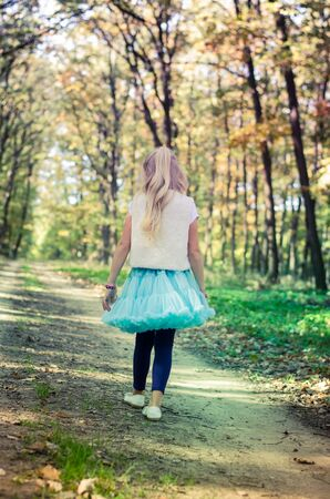 teenage girl in rural path among autumnal trees in forest walking away back view