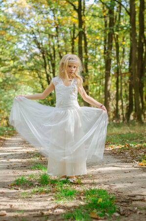cute little girl in long white wedding dress walking in magic forest