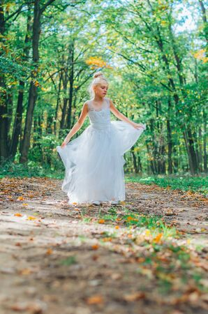 one little girl in dress dancing in path among autumnal trees in forest in golden hour atmosphere