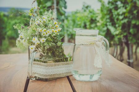flowers and refrestihg water in jar in spring vineyard in sunny day