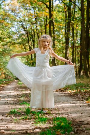 cute little girl in long white wedding dress
