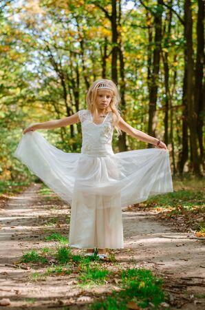 süßes kleines Mädchen im langen weißen Hochzeitskleid