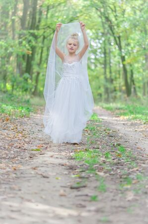 one little girl in dress posing in path among autumnal trees in forest in golden hour atmosphere